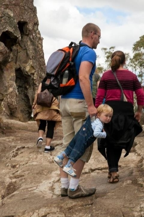 A baby is being dragged by the arm by a man while hiking