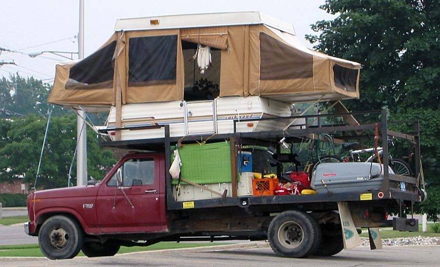 a distressed pickup truck is loaded with lots of camping gear and a rooftop tent