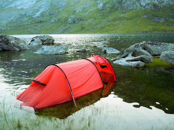 A tent is set up in several inches of water on a riverbank