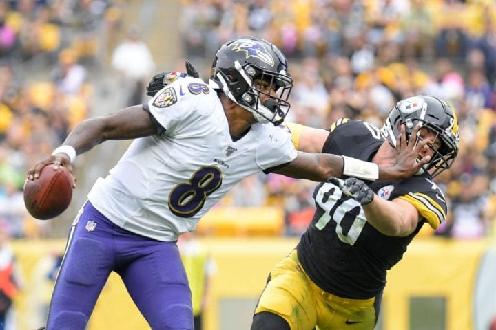 Baltimore Ravens quarterback Lamar Jackson (8) stiff-arms Pittsburgh Steelers outside linebacker T.J. Watt (90)
