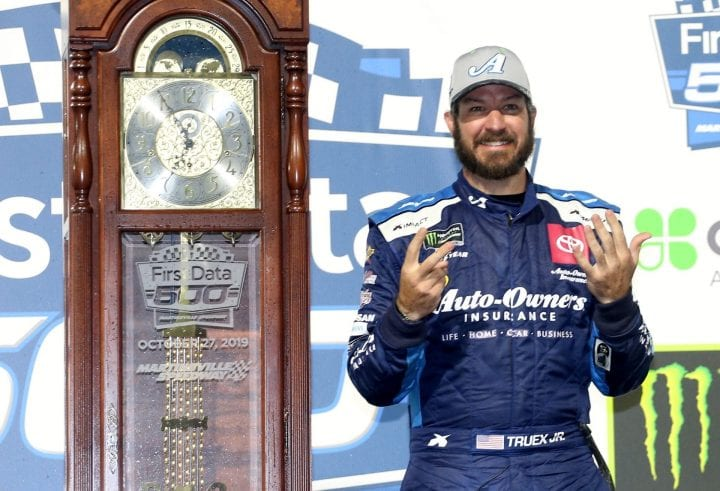 Martin Truex Jr, driver of the #19 Auto Owners Insurance Toyota, poses with the trophy in Victory Lane