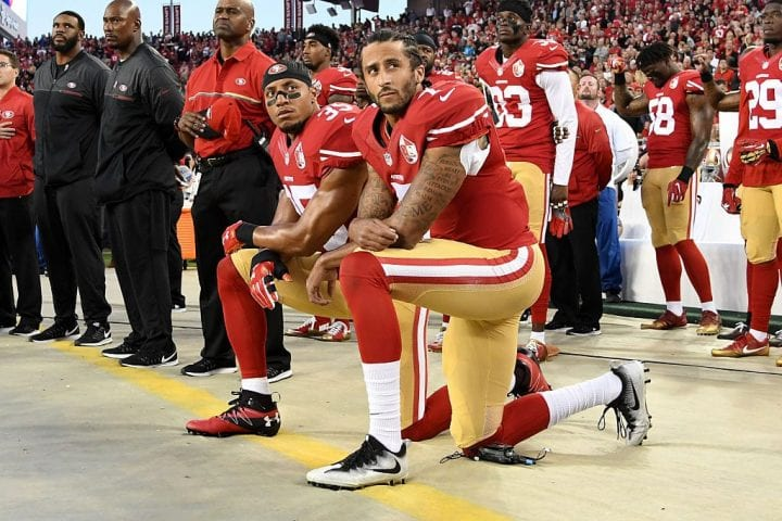 Colin Kaepernick #7 and Eric Reid #35 of the San Francisco 49ers kneel in protest