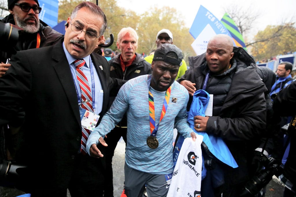Actor and comedian Kevin Hart is helped as he crosses the finish line during the TCS New York City Marathon in Central Park