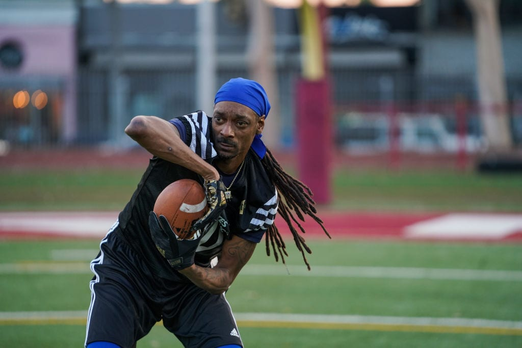 Snoop Dogg catches a football at the 5th Annual Athletes vs. Cancer celebrity flag football game