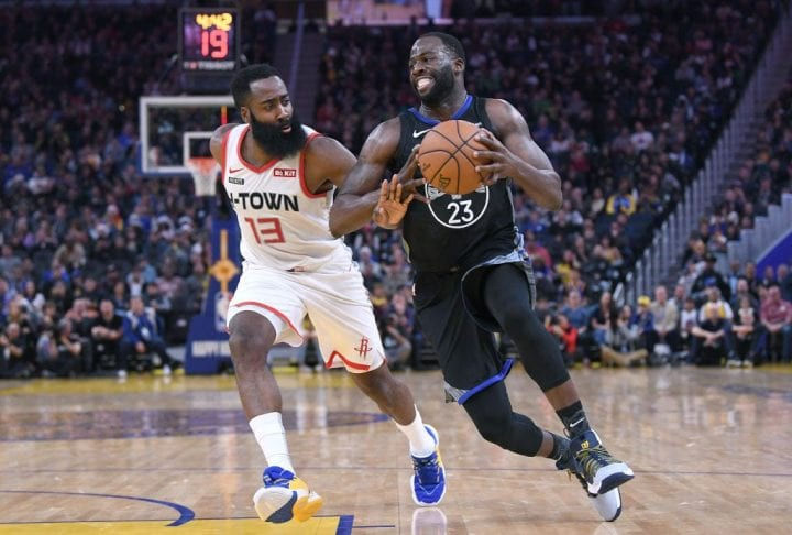 Draymond Green #23 of the Golden State Warriors drives towards the basket on James Harden #13 of the Houston Rockets