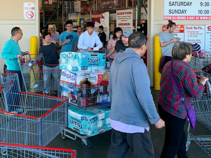 Shoppers buy toilet paper, food and water at a store, as people begin to panic buy and stockpile essentials from fear that supplies will be affected by the spread of the COVID-19, coronavirus outbreak across the country, in Los Angeles, California on February 29, 2020. - The US has suffered its first virus related death as the number of novel coronavirus cases in the world rose to 85,919, including 2,941 deaths, across 61 countries and territories. (Photo by Mark RALSTON / AFP)